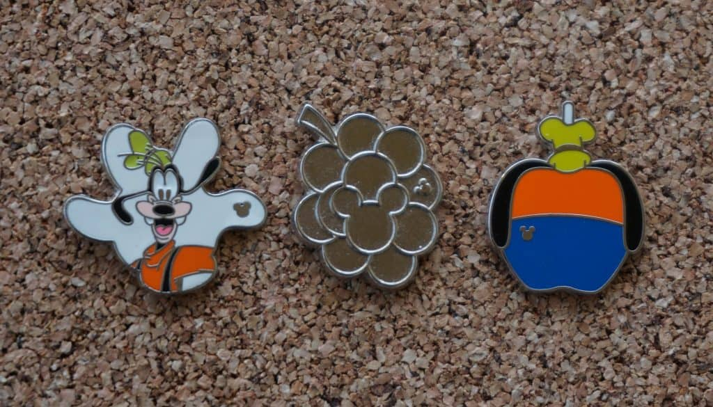 Hidden Mickey Disney pins displayed on corkboard.
